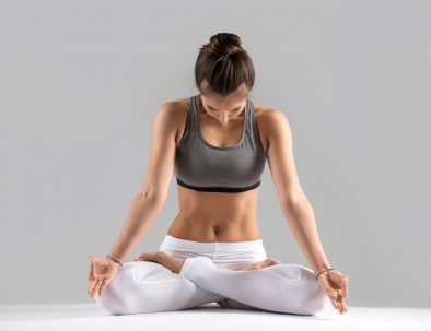 Young attractive woman practicing yoga, sitting in Lotus exercise, Padmasana pose, working out wearing sportswear, white pants, bra, indoor full length, isolated against grey studio background